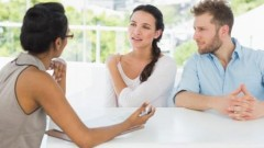Therapist talking with couple sitting at desk